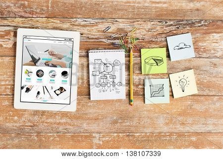 business, internet shopping, objects and technology concept - close up of notebook, tablet pc with online shop web page on screen and stickers on wooden office table
