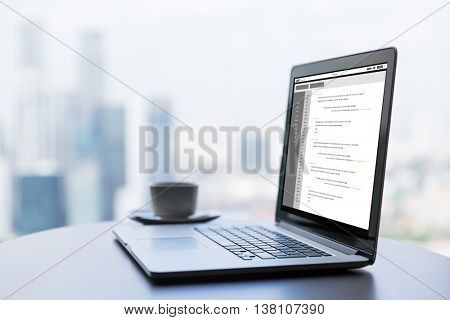 technology, programming, business and modern life concept- close up of open laptop computer with coding on screen and coffee cup on table at office or hotel room