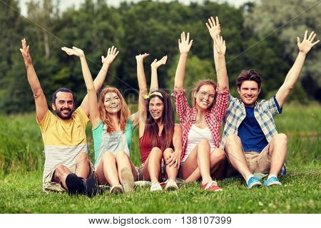 friendship, leisure, summer and people concept - group of smiling friends sitting on grass and waving hands outdoors