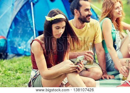travel, tourism, hike, technology and people concept - happy young woman with smartphone and friends at camping