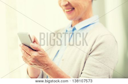 technology, communication, age and people concept - close up of happy senior woman with smartphone texting message at home