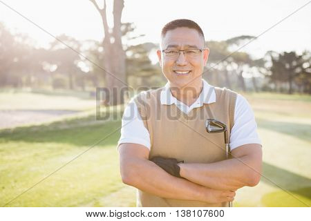 Portrait of golfer posing with his arms crossed on a field