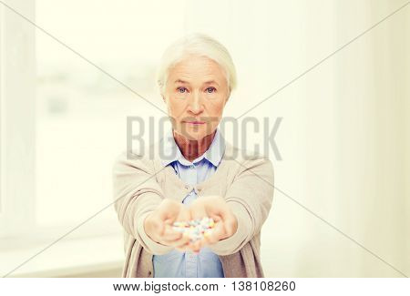 age, medicine, health care and people concept - senior woman with pills at home or hospital office