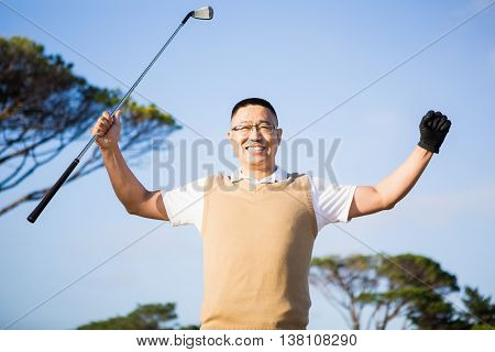 Golfer raising his hands on a field