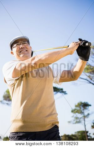 Low angle view of sportsman playing golf on a field