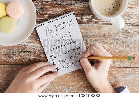 business, education and people concept - close up of female hands with pencil, coffee and cookies solving task or writing mathematical equation to notebook