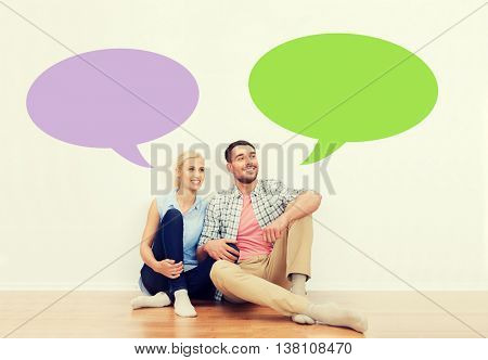 home, people, repair, moving and real estate concept - happy couple of man and woman sitting on floor at new place with empty blank text bubbles