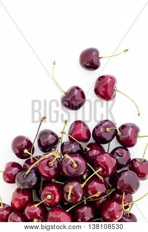 Fresh red cherries on a white surface seen from above with blank space.