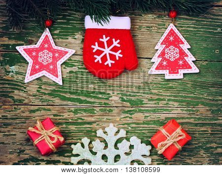 New year background with branch spruce decoration glove star christmas tree and gift box on a wooden table retro style