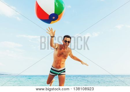 Young handsome man at the beach trowing the ball into the camera