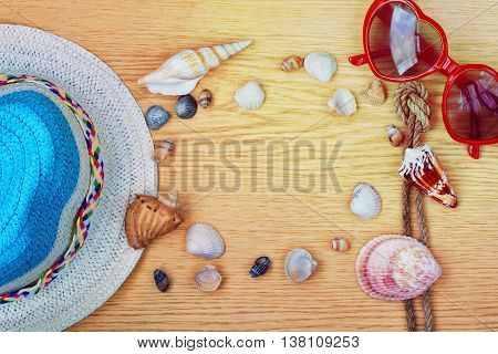 background with summer straw hat sun glasses and seashells vacation concept