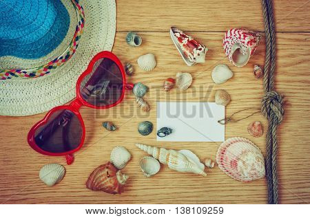 background with summer straw hat sun glasses and seashells paper label vacation concept