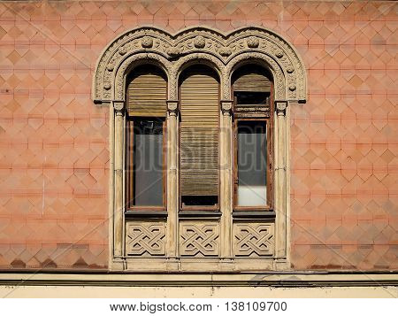 Old window in the Byzantine style. Triple arched window  with wooden jalousie on the wall of red bricks in an old building.