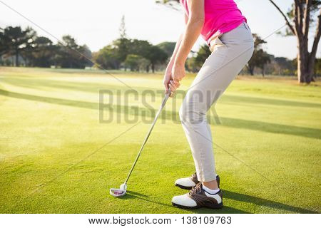 Close up of woman golfer preparing her shot on a field