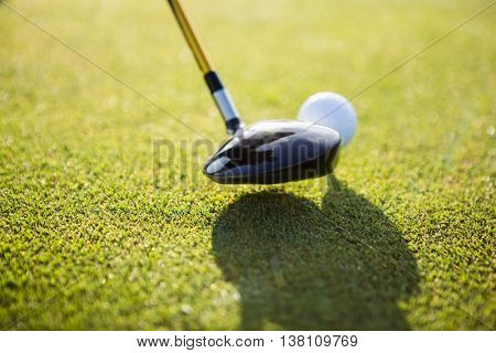 Close up of a golf ball and club on field
