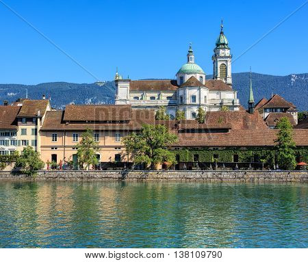 View on the city of Solothurn in Switzerland over the Aare river with the towers of the St. Ursus cathedral in the background.