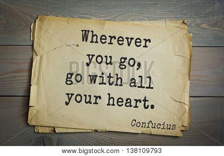 Ancient chinese philosopher Confucius quote on old paper background. Wherever you go, go with all your heart.