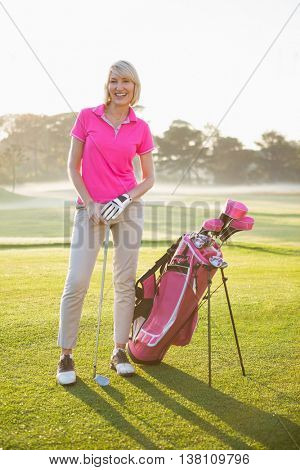 Woman golfer posing with her golf equipments on field
