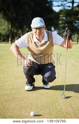 Portrait of golfer crouching and looking his ball on field