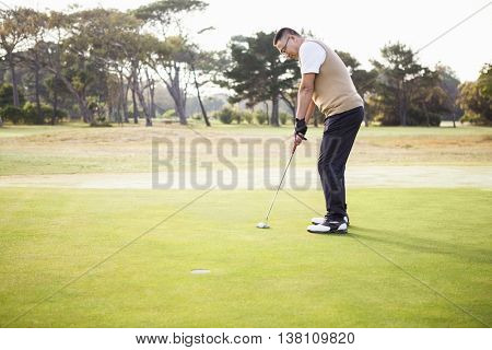 Profile view of sportsman playing golf on a field