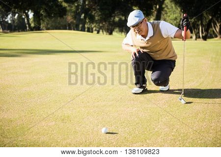 Side view of golfer crouching and looking his ball on field