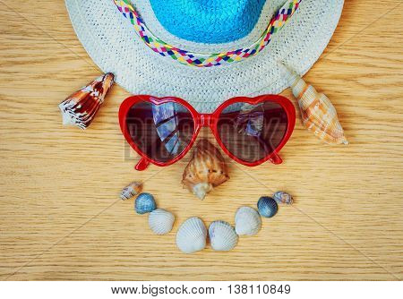 funny face of hat glasses and seashells on wooden table vacation concept