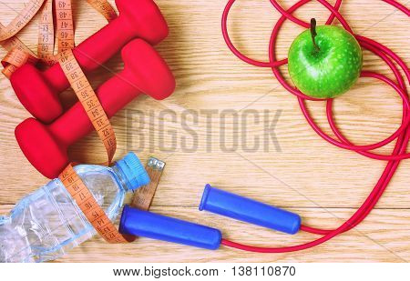 dumbbells apple bottle of water measuring tape and skipping rope on wooden planks fitness concept top view