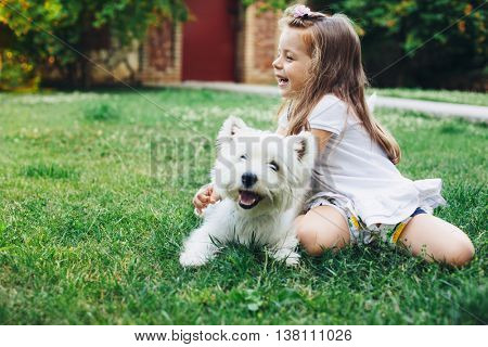 Child playing with English Highland White Terrier dog on grass in the backyard