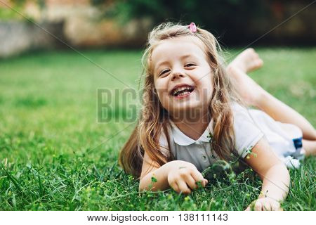 Child relaxing on green grass in the backyard.
