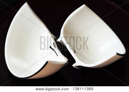 View of a white broken cup and fractured shards of sharp glass fragments scattered on black background. Concept for divorce, relationships, friendships. Horizontal