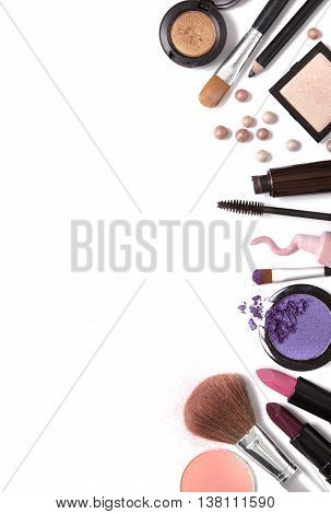 A selection of make up products isolated on a white background forming a page border