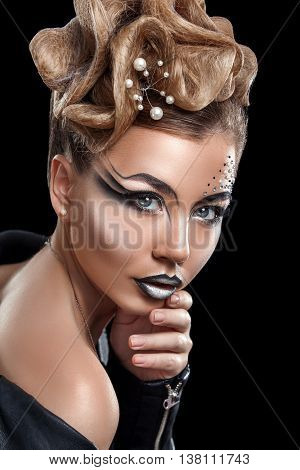 Beauty woman with beautiful make-up color . Blond hair raised hair jewelry on his neck clean skin beautiful face . Portrait shot in studio on a dark background .
