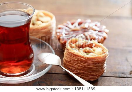 Set of various cakes near tea on nice wooden background
