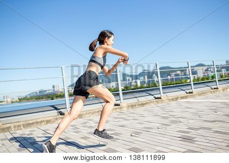 Woman using waerable smart watch and running at city