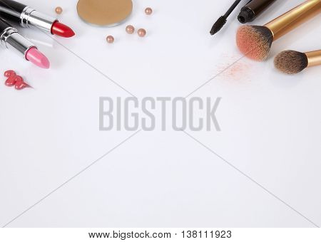 A selection of make up products arranged on a white background forming a page header