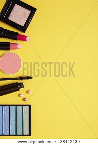 A selection of make up products arranged on a yellow background forming a page border