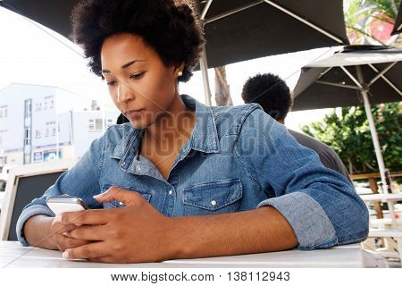 Young Woman Sitting And Using Cell Phone Outside