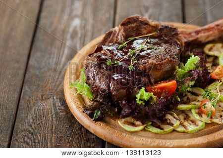 Bbq pork rib with grilled vegetables on cutting board, brown wooden background, free space