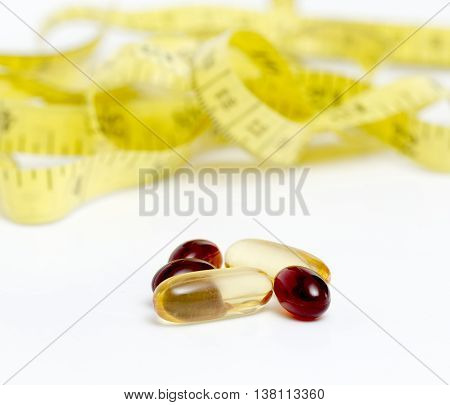 Picture of a Cod liver oil omega 3 gel and krill oil capsules in front of yellow tape measure