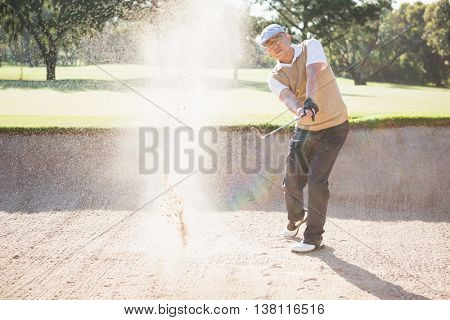 Sportsman playing golf on a sandbox