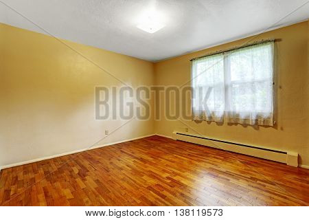 Small Empty Basement Room With Hardwood Floor And Beige Walls