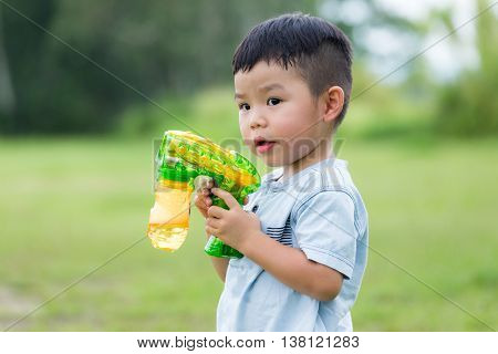 Asian little boy play with bubble blower gun at outdoor
