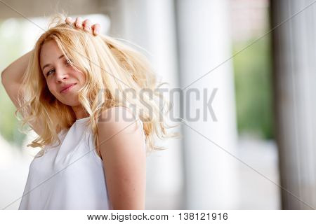 Portrait of young woman with long blonde curly hair, model standing in profile and touching her hair