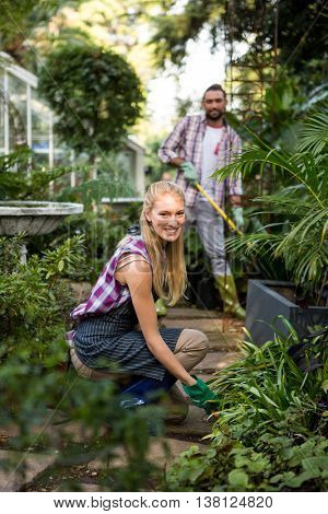 Portrait of happy young female gardener with colleague in community garden
