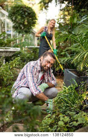 Portrait of happy young male gardener with colleague in community garden