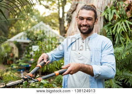 Portrait of happy young male gardener using hedge clippers at community garden
