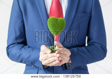 Businessman In Suit Holding A Green Heart Shape