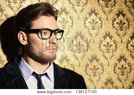 Portrait of a handsome young man standing by a golden vintage wallpaper. Luxury. Men's beauty, fashion.