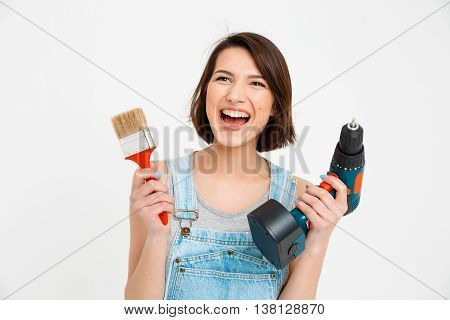 A portrait of young  beautiful girl, in gray shirt and denim overall, screaming, holding painting brush and drill, looking at camera, isolated on white background