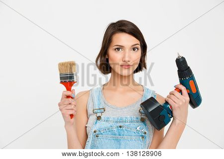 A portrait of young  pretty girl, in gray shirt and denim overall, holding painting brush and drill, seriously looking at camera, isolated on white background